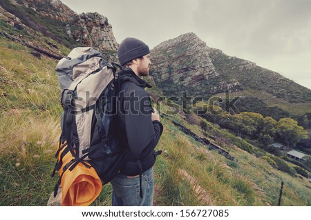Adventure man hiking wilderness mountain with backpack, outdoor lifestyle survival vacation