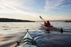 Adventure Man on a Sea Kayak is kayaking during a vibrant and colorful winter sunset. Taken in Vancouver, British Columbia, Canada. Adventure, Vacation Concept
