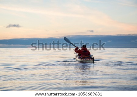 Adventure Man on a Sea Kayak is kayaking during a vibrant and colorful winter sunset. Taken in Vancouver, British Columbia, Canada. Adventure, Vacation Concept #1056689681
