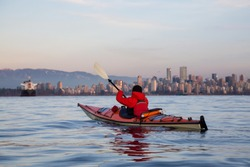 Adventure Man on a Sea Kayak is paddline during a vibrant winter sunset with Downtown City Skyline in the background. Taken in Vancouver, British Columbia, Canada.