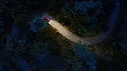 Adventure night road trip in the forest, aerial view of a car headlights on deep jungle road. Mystery concept.
