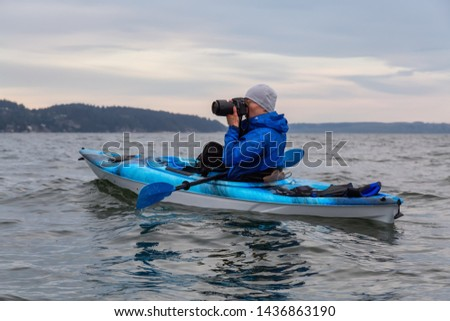 Adventure photographer taking pictures with his camera from a kayak in the ocean. Taken in Howe Sound near Horseshoe Bay, West Vancouver, British Columbia, Canada.