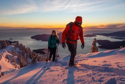 Adventure seeking man and woman are hiking to the top of a mountain during a vibrant winter sunset. Taken in Mnt Harvey, North of Vancouver, BC, Canada.