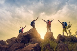 Adventure to overcome the limits of life, male and female hikers climbing up mountain cliff under sunrise. they are success full at top the mountain. helps and team work concept.