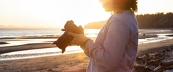 Adventure Travel Photographer at West Pacific Ocean Coast. Colorful Sunny Sunset. Adult White Caucasian Woman. Location: White Rock, Greater Vancouver, BC, Canada.