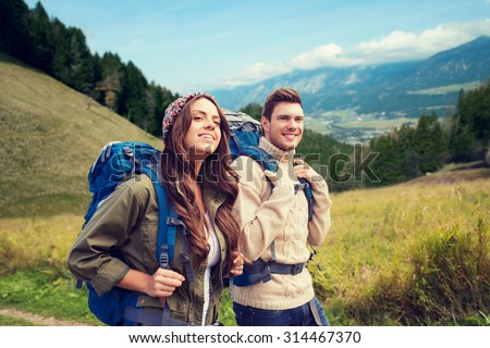 adventure, travel, tourism, hike and people concept - smiling couple walking with backpacks over alpine hills background #314467370