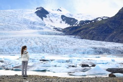 Adventure woman by glacier nature on Iceland. Tourist in Icelandic sweater by glacial lagoon / lake of Fjallsarlon, Vatna glacier, Vatnajokull National Park. Young woman visiting nature landscape.