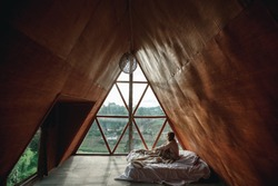 Adventure young girl in a wooden cabin  enjoy landscape through the window. Woman is sitting on bed in ethnic wooden house in room under the roof in the morning