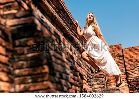 Adventures are to the adventurous. Young woman posing beside ancient ruins in Asia. Copy space on the left side