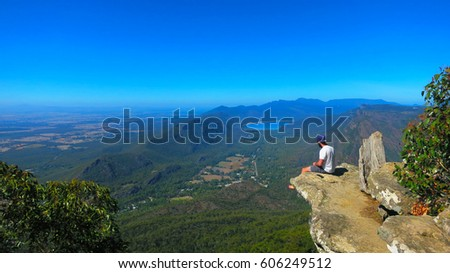 Adventurous brave young man sitting on a high cliff edge rock at the top of the Boroka Lookout view at the The Grampians National Park (Gariwerd), Victoria, Australia Stock photo ©