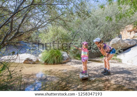 adventurous family: five years old girl pointing with magnifying glass next to her mother, with caps, discovering nature in a river of Camorza Gorge (Madrid, Spain, Europe) #1258347193
