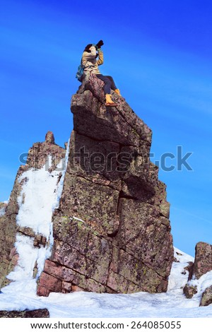 Adventurous female photographer is sitting on a rock pinnacle while shooting. Travel, adventure, active recreation concept.