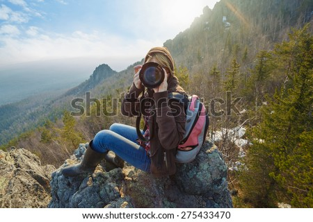 Adventurous female photographer sitting on the rock while photographing mountains facing the off scene viewer against the setting sun. Wide angle perspective. Tourism, adventure, hiking concept.