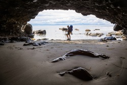 Adventurous girl hiking in a cave on Juan de Fuca Trail to Mystic Beach on the Pacific Ocean Coast during a sunny summer day. Taken near Port Renfrew, Vancouver Island, BC, Canada.