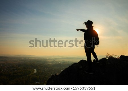 Adventurous Girl in black on top of a mountain with a beautiful sunrise. Mountains and people. Adventure and travel.