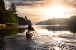 Adventurous Girl kayaking in the Pacific Ocean. Sunset Sky Art Render. Taken in San Josef Bay, Cape Scott, Northern Vancouver Island, British Columbia, Canada. Adventure Travel Concept