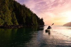 Adventurous Girl kayaking in the Pacific Ocean. Sunset Sky Art Render. Taken in San Josef Bay, Cape Scott, Northern Vancouver Island, British Columbia, Canada. Adventure Travel Concept