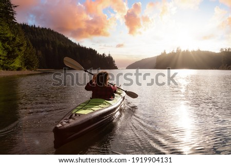 Adventurous Girl kayaking in the Pacific Ocean. Sunset Sky Art Render. Taken in San Josef Bay, Cape Scott, Northern Vancouver Island, British Columbia, Canada. Adventure Travel Concept ストックフォト ©