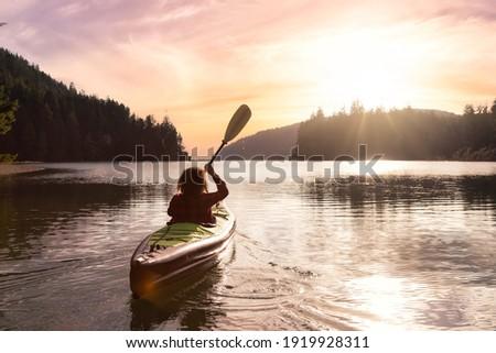Adventurous Girl kayaking in the Pacific Ocean. Sunset Sky Art Render. Taken in San Josef Bay, Cape Scott, Northern Vancouver Island, British Columbia, Canada. Adventure Travel Concept ストックフォト ©