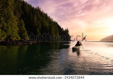 Adventurous Girl kayaking in the Pacific Ocean. Sunset Sky Art Render. Taken in San Josef Bay, Cape Scott, Northern Vancouver Island, British Columbia, Canada. Adventure Travel Concept Foto stock ©