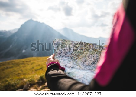 Adventurous Girl navigating in with a Topographic Map in the beautiful Mountains of the Austrian Alps #1162871527