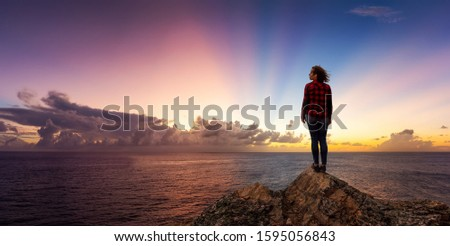 Adventurous Girl on a Rocky Ocean Coast enjoying the beautiful view of the Colorful Sunset. Panoramic Image Composite. Adventure, Travel, Explore Concept.