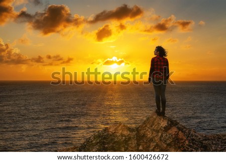 Adventurous Girl on a Rocky Ocean Coast enjoying the beautiful view of the Colorful Sunset. Image Composit. Adventure, Travel, Explore Concept.