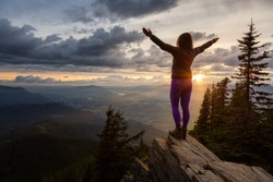 Adventurous Girl on top of a Rocky Mountain overlooking the beautiful Canadian Nature Landscape during a dramatic Sunset. Taken in Chilliwack, East of Vancouver, British Columbia, Canada.
