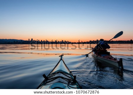 Adventurous Girl Sea Kayaking during a vibrant winter sunrise with City Skyline in Background. Taken in Downtown Vancouver, British Columbia, Canada. #1070672876