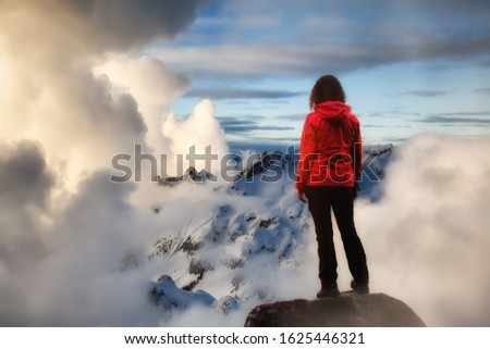 Adventurous Girl watching the Beautiful Dramatic Sunset on top of the Mountains. Composite Image.  Landscape taken in British Columbia, Canada. Concept: Adventure, Art, Travel, Hike, Outdoors, Sport