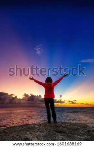 Adventurous Girl with open hands on a Rocky Ocean Coast enjoying the beautiful view of the Colorful Sunset. Image Composit. Adventure, Travel, Explore, Freedom Concept.