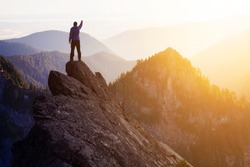 Adventurous Man Hiker With Hands Up on top of a Steep Rocky Cliff. Sunset or Sunrise. Composite. Landscape Taken from British Columbia, Canada. Concept: Adventure, Explore, Hike, Lifestyle