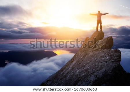 Adventurous Man Hiker With Hands Up on top of a Steep Rocky Cliff. Sunset or Sunrise. Landscape Taken from British Columbia, Canada. Concept: Adventure, Explore, Hike, Lifestyle. Composite.  Foto stock ©