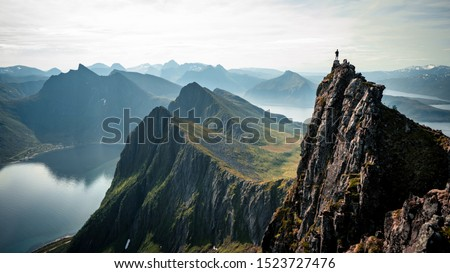 Adventurous man is standing on top of the mountain and enjoying the beautiful view during a vibrant sunset. Beautiful Nature Norway natural landscape aerial photography Stock photo ©