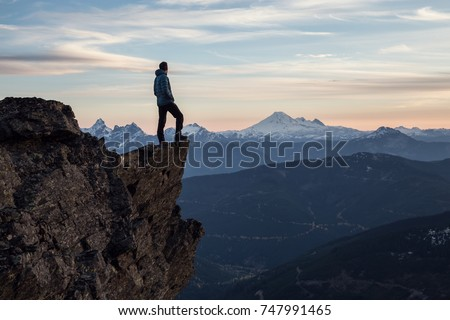 Adventurous man is standing on top of the mountain and enjoying the beautiful view during a vibrant sunset. Taken on top of Cheam Peak in Chilliwack, East of Vancouver, BC, Canada.