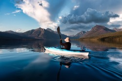 Adventurous Man Kayaking in Lake McDonald with American Rocky Mountains in the background. Colorful Sunset Sky. Taken in Glacier National Park, Montana, USA.