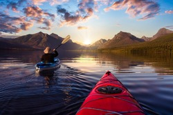 Adventurous Man Kayaking in Lake McDonald with American Rocky Mountains in the background. Colorful Sunrise Sky Art Render. Taken in Glacier National Park, Montana, USA.