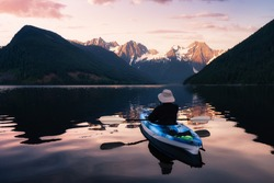 Adventurous man kayaking in the water surrounded by the Beautiful Canadian Mountain Landscape. Sunset Artistic Render. Taken in Jones Lake, near Hope, East of Vancouver, BC, Canada.