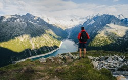 Adventurous man on the edge of a cliff overlooking the beautiful Austria Alps and Lake during a vibrant summer sunset. Taken in Hiking to the Olperer Hut in the Zillertal Alps in Austria