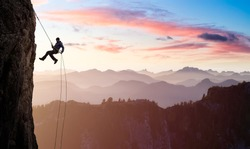 Adventurous Man Rappelling from Cliff. Aerial view of the mountains during a colorful and vibrant sunset or sunrise. Landscape taken in British Columbia, Canada. composite. Concept: Adventure