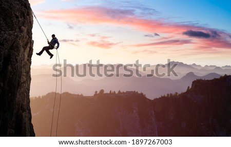 Adventurous Man Rappelling from Cliff. Aerial view of the mountains during a colorful and vibrant sunset or sunrise. Landscape taken in British Columbia, Canada. composite. Concept: Adventure Photo stock ©
