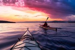 Adventurous Man Sea Kayaking in the Pacific Ocean. Dramatic Colorful Sky Art Render. Taken in Jericho, Vancouver, British Columbia, Canada.