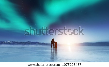 Adventurous man standing on a frozen lake with a backpack, looking at northern lights. Travel and adventure.