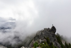 Adventurous Man Standing on top of a rugged rocky mountain during a cloudy summer morning. Taken on Crown Mountain, North Vancouver, BC, Canada.