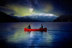 Adventurous People on a Red Canoe in a Lake. Night Sky with Stars and Northern Lights. Dream Mood. Landscape taken in Harrison Hotsprings, British Columbia, Canada.