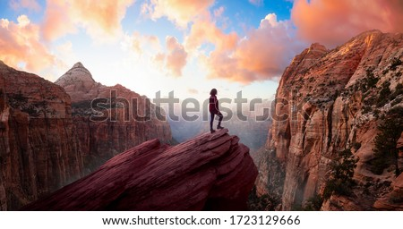 Adventurous Woman at the edge of a cliff is looking at a beautiful landscape view in the Canyon during a vibrant sunset. Taken in Zion National Park, Utah, United States. Sky Composite Panorama Stockfoto ©