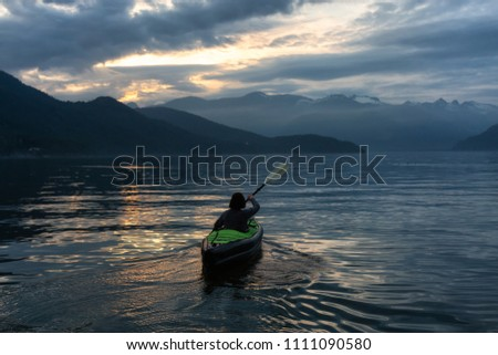 Adventurous woman kayaking during a vibrant sunset surrounded by Canadian Mountain Landscape. Taken in Howe Sound, North of Vancouver, BC, Canada. #1111090580