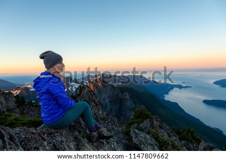 Adventurous woman on top of a mountain cliff is enjoying the beautiful summer sunrise. Taken on Mount Brunswick, Lions Bay, North of Vancouver, BC, Canada. #1147809662