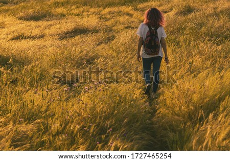 Adventurous Woman, Walking With Her Backpack Through The Fields Of Extremadura, Spain. Beautiful Natural Landscape In Extremadura With Its Colors And Wild Flowers. Lifestyle.
