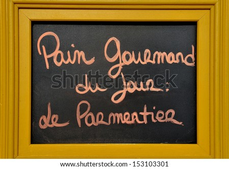 """Advertisement board at a French bakery.The text tells the people in French that the bread of the day is called :""""le Parmentier""""."""